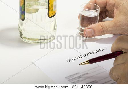 Unhappy man drinking spirit beacuse reading divorce agreement