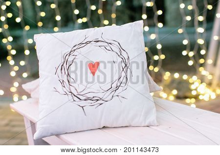 indoor, house, rest concept. on the background of beautiful magestic blurs there is white pillow with nice print in form of heart surrounded by wreath of brunches without leaves