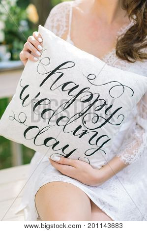decoration, wedding, outdoors concept. young caucasian woman with dark curly hair holding white original pillow with words of congratulation with day of engagement