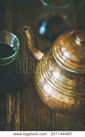 Oriental Middle Eastern vintage copper hummered tea pot and black tea in traditional tulip glasses over rustic wooden background, selective focus, vertical composition