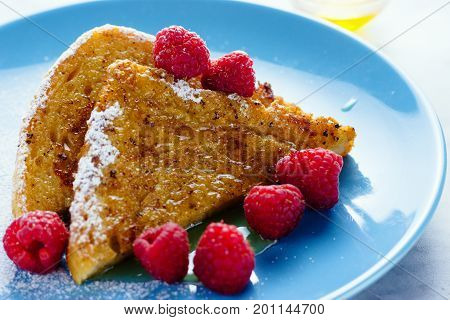 Halved slice of french toast with raspberries and honey on blue plate