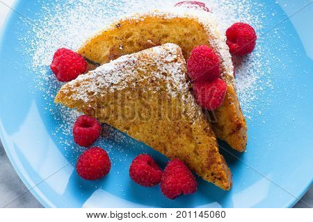 Fresh french toast richly covered by powdered sugar and raspberries