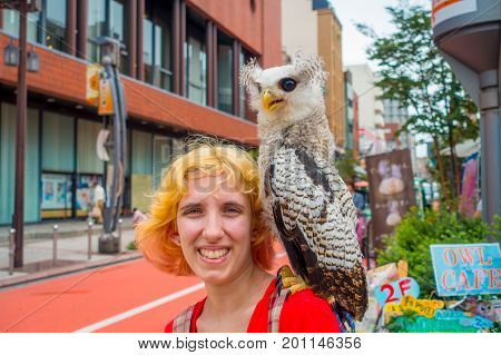 TOKYO, JAPAN JUNE 28 - 2017: Portrait of a smiling woman with a beautiful owl posing over a shoulder in the street in Akihabara owl cafe - owls are very popular pets in Japan.