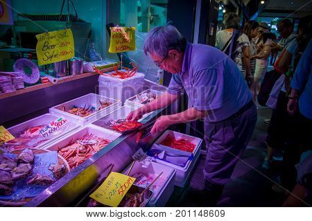 TOKYO, JAPAN JUNE 28 - 2017: Unidentified man using his hands to hold a white plastic tray with red shrimps at the Fish Market Tsukiji wholesale in Tokyo Japan, Tsukiji Market is the biggest wholesale fish and seafood market in the world.
