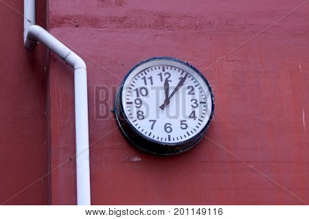 Clock on red brick wall on an old abandoned factory