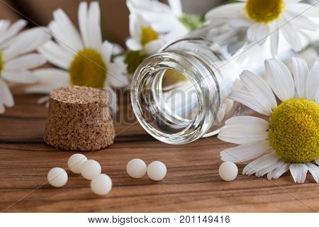 A Bottle Of Homeopathic Globules With Chamomile Flowers
