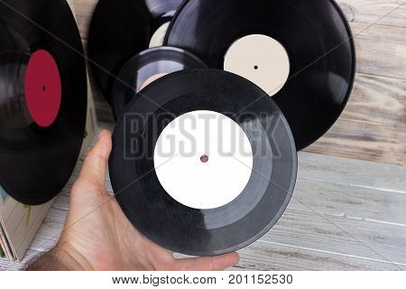 The man's hand holds an Old vinyl record and a collection of albums.