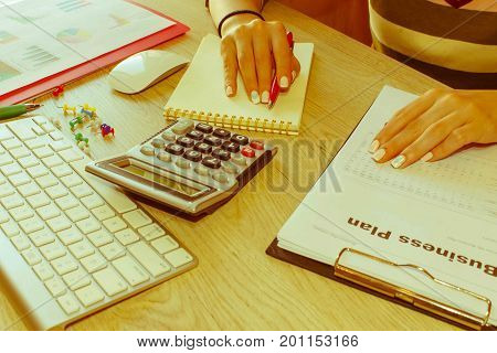 Female Studying Plans In Office. Business woman working at the office. calculating or checking balance. Business plan finances investment economy saving money or insurance concept - Retro color