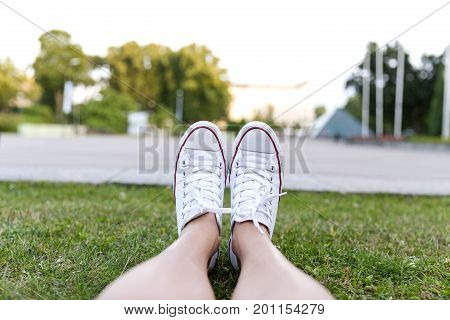 Sneakers on green grass in city park