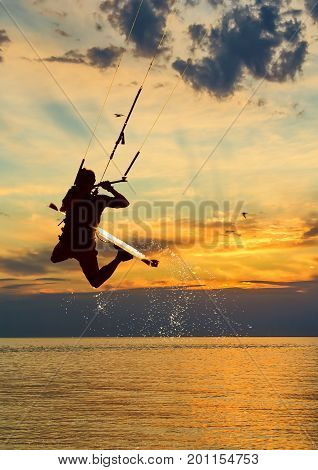 Silhouette of kitesurfer jumping over the sea on sunset sky background