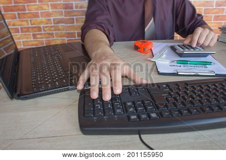Businessman using a calculator to calculate the numbers. Accounting Accountancy Calculation Concept. Male using a tablet to analysis marketing