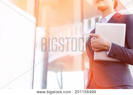 Midsection of businesswoman holding tablet PC by glass wall