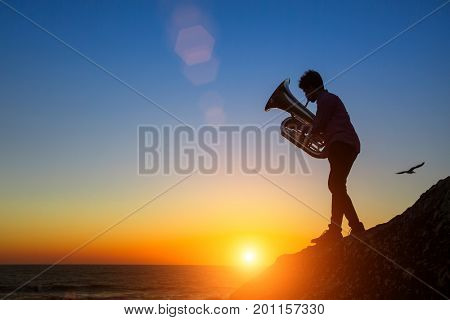 Silhouette of man play Tuba on sea shore at amazing sunset.