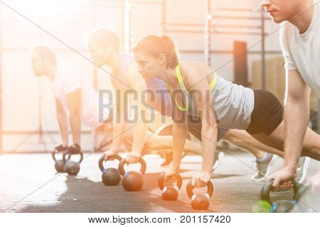 Determined people doing pushups with kettlebells at crossfit gym