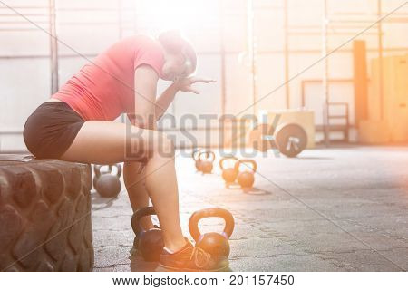 Exhausted woman sitting on tire in crossfit gym