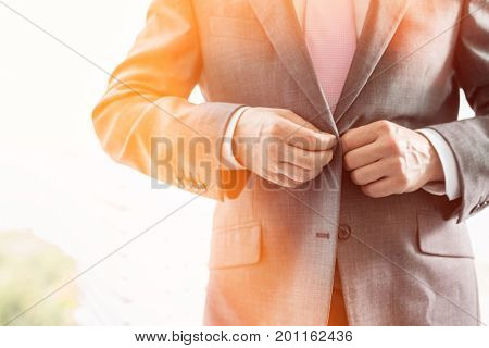 Midsection of mature businessman buttoning his blazer