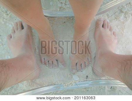 Pair of feet on the white sand beach