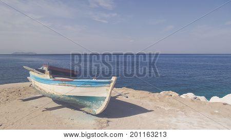 Fishing boat sitting on the shore of aegean sea