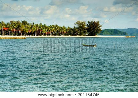 Fishing boat rowing alone in the middle of a bay with an island in the background. Perfect for a shipwrecked representation or a place to unwind