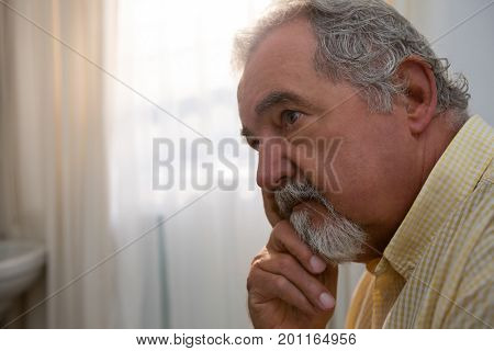 Close up of thoughtful senior man relaxing at retirement home
