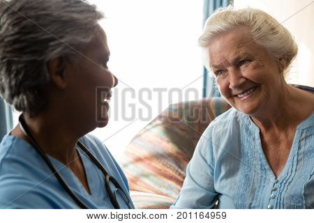 Smiling nurse talking to senior patient in nursing home