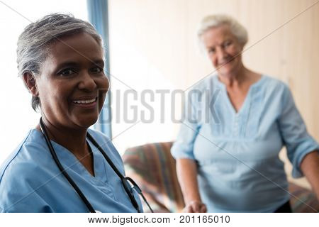 Portrait of nurse and senior patient standing in retirement home