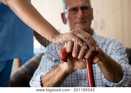 Close up of female doctor and senior man hands holding walking cane in retirement home