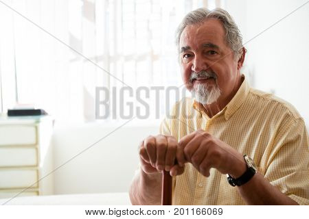 Portrait of happy senior man holding walking cane while sitting in nursing home