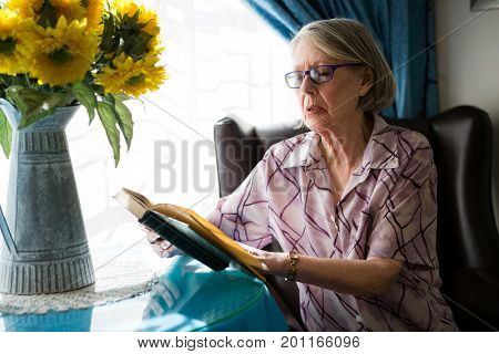 Senior woman reading book while sitting on armchair in retirement home
