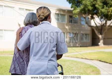 Rear view of doctor assisting senior woman in walking at park