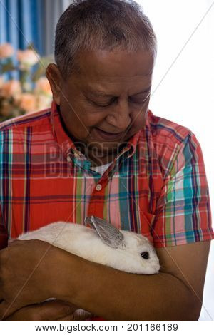 Close up senior man holding rabbit at retirement home