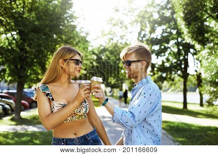 Romantic cute young couple wearing stylish clothing and black sunglasses clinking papercups of coffee while having fun outdoors walking in park enjoying good sunny day. Love and togetherness