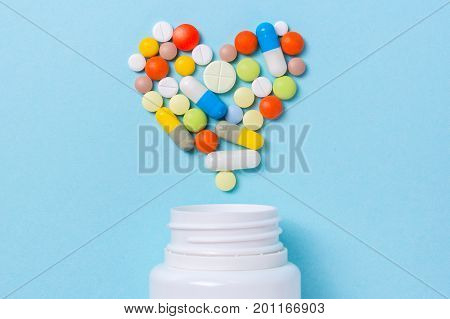 Assorted pharmaceutical medicine pills tablets and capsules for the treatment of heart disease. Heart shape and bottle of pills