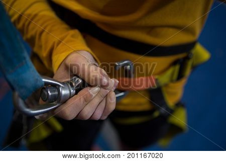 Mid section of woman tightening hook in fitness studio