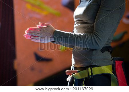 Mid section of woman rubbing powder on hands in fitness studio
