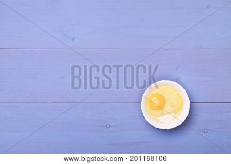 Wooden table top view. On the table are the food for cooking. Healthy food. Dietetic foods. Above view on food. egg and flour in a bowl on wooden table