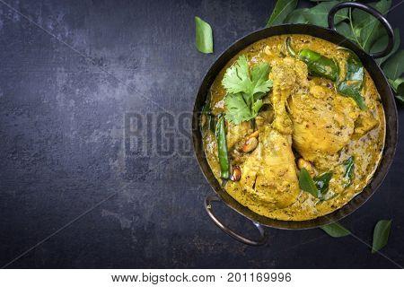 Traditional Indian curry chicken as close-up in a Korai with copy space left