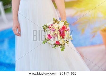 Bride in wedding dress holds her rouses bouquet against blue pool