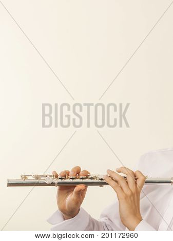Flute music playing professional male flutist musician performer. Young elegant guy holding instrument in hands. Copy space for text