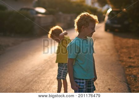 Two curious little curly boys on the street