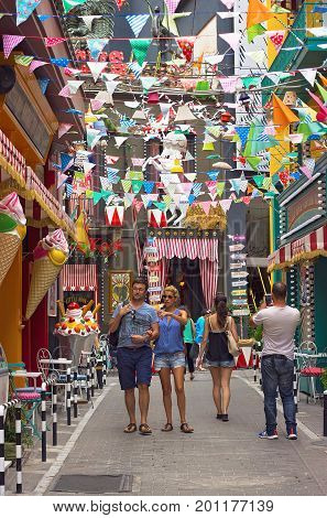 ATHENS GREECE - JULY 16 2017: Man and woman taking pictures of colorful decorated streets at Psiri area Athens city near Monastiraki