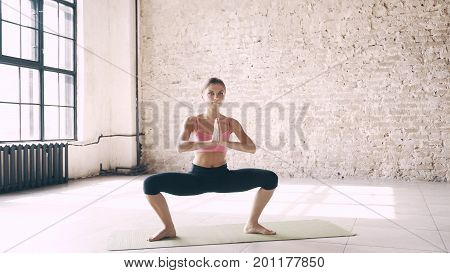 A beautiful, smart, athletic girl does yoga exercises in a gym in loft style, with natural light from large windows. She is dressed in a sporty uniform, breeches and crocheted top. Stretching, flexibility and equal weight.