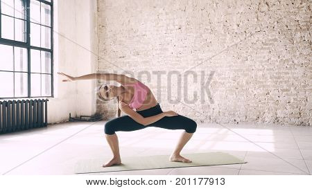 Yoga standing. A beautiful, smart, athletic girl does yoga exercises in a gym in loft style, with natural light from large windows. She is dressed in a sporty uniform, breeches and crocheted top. Stretching, flexibility and equal weight.