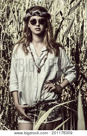 Beautiful hippie girl stands among the reeds. Spirit of freedom. Fashion shot. Bohemian, bo-ho style. Sepia portrait.