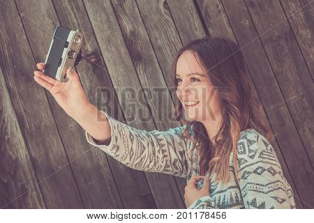Portrait of young beautiful female taking self portrait by using retro vintage film camera against wooden background