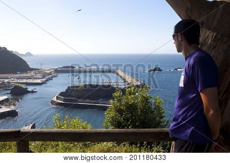 guy looking to a port full of boats in Cudillero Spain