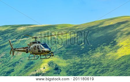 Helicopter with broadcasting equipment flying at high altitude in Pyrenees Mountains.