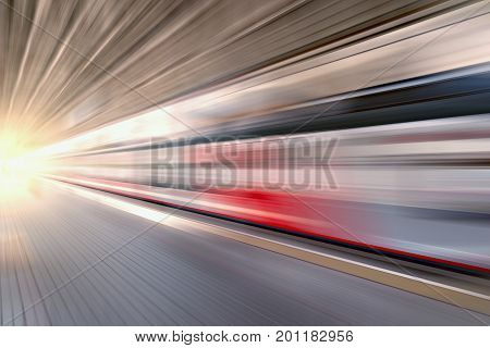 Modern high-speed train moves fast along the platform