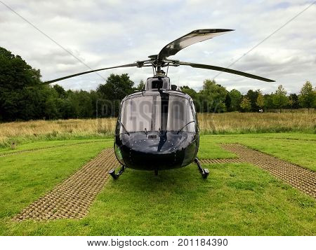 Front view of a black squirrel helicopter that landed on the H helicopter landing spot. With grass and trees in the background.