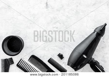 hairdresser working desk space with dryer and tools for hair styling on gray stone desk background top view mock up